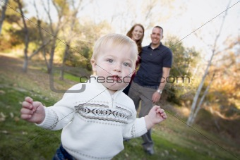 Cute Young Boy Walking in the park as Adoring Parents Look On From Behind.