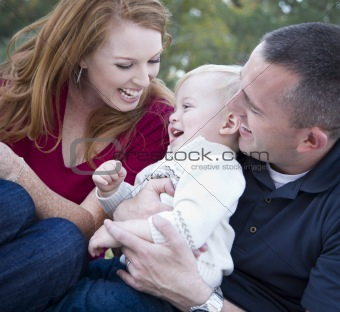 Attractive Young Parents Laughing with their Child Boy in the Park.