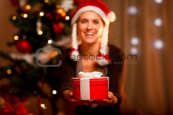 Hand presenting gift box and smiling woman and Christmas tree in background
