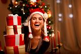 Portrait of laughing woman near Christmas tree looking out from pile of present boxes