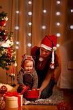 Young mother with happy baby opening present box near Christmas tree