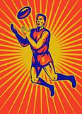 aussie rules player jumping catching ball