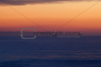 Offshore Oil Rig Drilling Platforms at Sunset