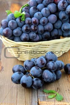 black sweet grapes on wooden table