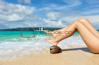 Women&#39;s legs on a beach