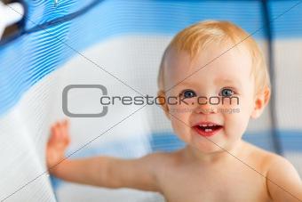 Portrait of happy baby in playpen