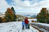 First winter snow in autumn mountain and family on walk