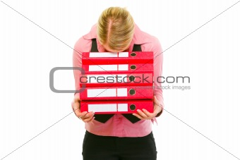 Tired female business clerk put her head on folders stack