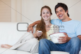 Couple watching television while eating popcorn