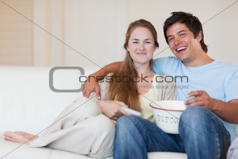 Smiling couple watching television while eating popcorn