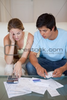 Portrait of a worried couple looking at their bills