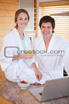 Portrait of a charming couple having breakfast while using a notebook