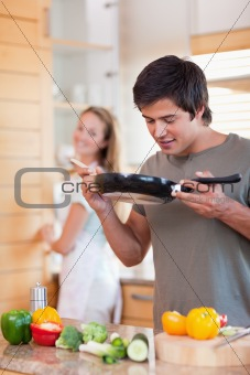 Portrait of a man cooking while his fiance is washing the dishes