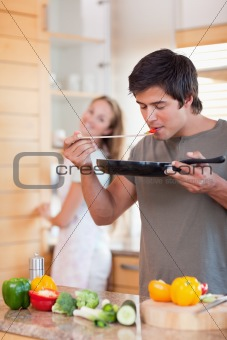 Portrait of a man cooking while his girlfriend is washing the dishes