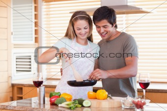 Couple cooking dinner while drinking red wine