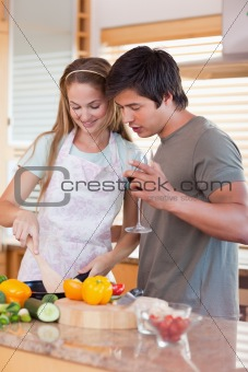 Portrait of a couple cooking while drinking wine
