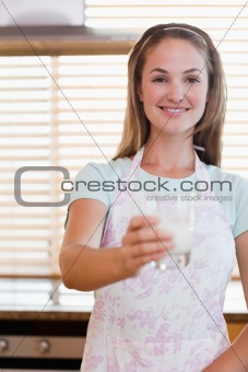 Portrait of a young woman giving a glass of milk