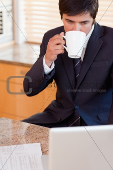 Portrait of a businessman drinking coffee while using a laptop
