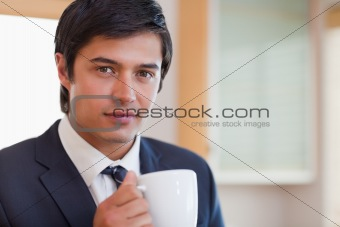Close up of a handsome businessman drinking coffee