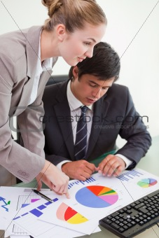 Portrait of a serious business team studying statistics with a computer