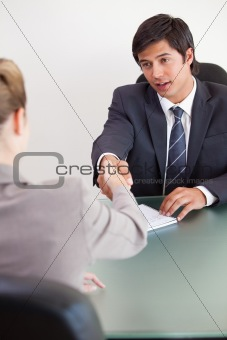 Portrait of a manager shaking the hand of a customer