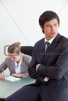Portrait of a manager posing while his colleague is working