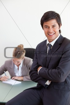 Portrait of an office worker posing while his colleague is working