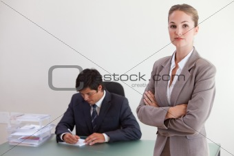 Busineswosman posing while her colleague is working