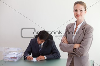 Young busineswosman posing while her colleague is working