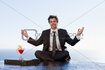 Smiling businessman relaxing in the lotus position