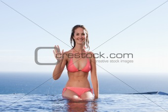 Young woman sitting by a swimming pool