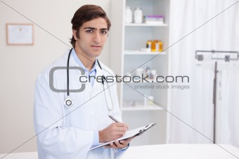 Male doctor with clipboard and pen