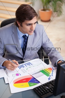 Businessman analyzing statistics at his desk