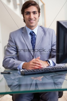 Smiling businessman sitting at his computer