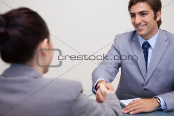 Business partners sitting at a table shaking hands