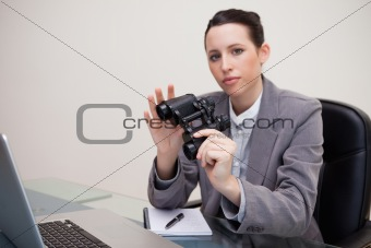 Businesswoman on her desk with binoculars