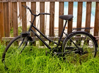 black grunge bicycle aged on a wood fence