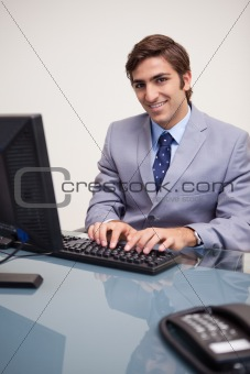 Smiling businessman typing on his keyboard