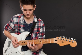 Young male playing electric guitar