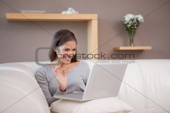 Cheerful woman with her notebook on the sofa