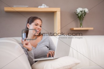Smiling woman shopping online on the sofa