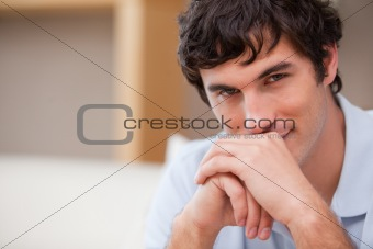 Man with hands folded in the living room