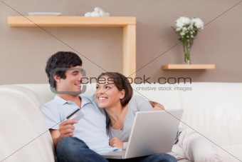 Cheerful couple booking holiday online