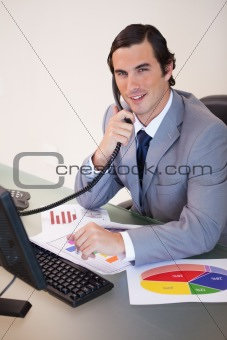 Smiling businessman on the phone working on statistics