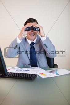 Businessman at his desk looking through binoculars