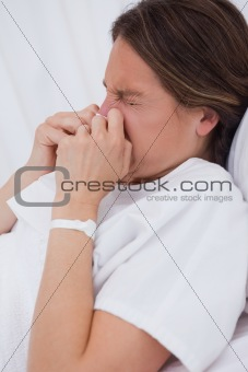 Side view of women in bed sneezing
