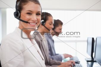 Smiling call center agent colleagues behind her