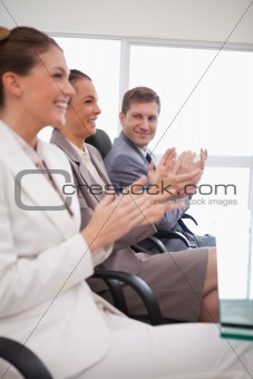 Side view of business team applauding