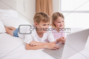 Smiling children using a notebook