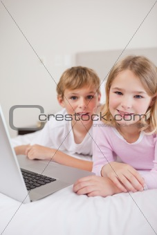 Portrait of cute children using a laptop